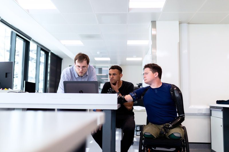 Engineers look at computer screen with prosthetic limb user